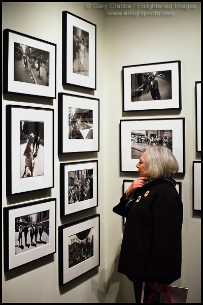 Photo: Woman looking at a photographic art display Photos by Garry Winogrand at the Pier 24 Gallery in San Francisco, California